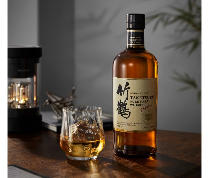 Bottle of Nikka-Taketsuru whisky on a bar with a glass of whisky beside it