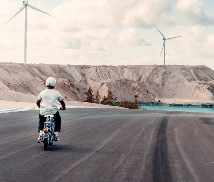Man riding motorbike with wind turbines in distance