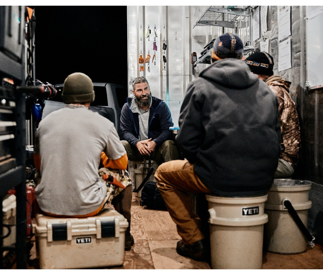 Company founder Jake Muise gathers at night with his crew of employees in a mobile work space at night