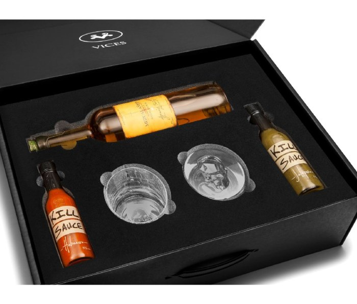Vices black gift container filled with a liquor bottle, glasses, and two mini bottles of hot sauce