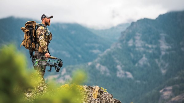 Hunter standing over ridge with bow