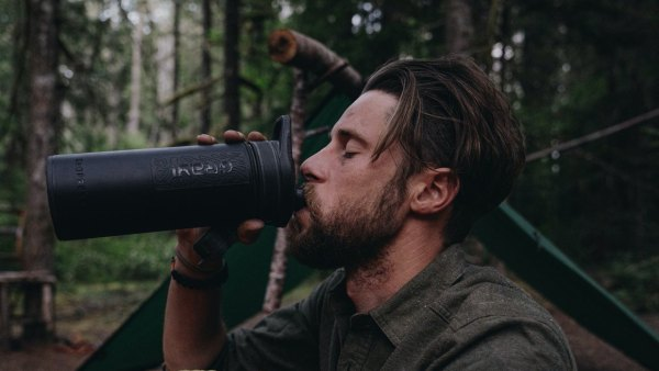 water filtration devices man drinking at a camp site