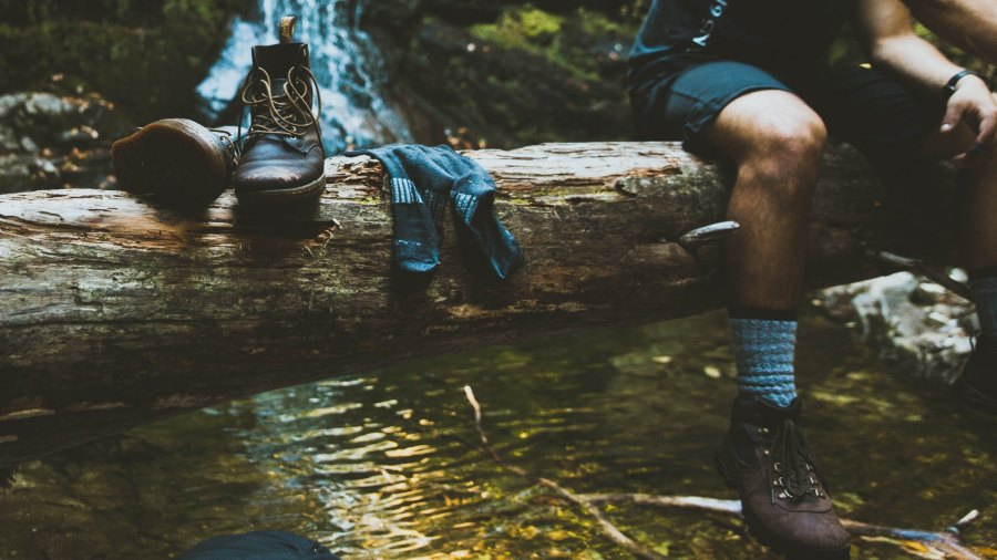 man resting on a log with wool socks