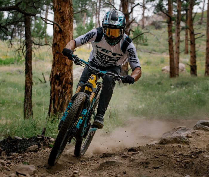 Man riding electric mountain bike in full helmet and goggles