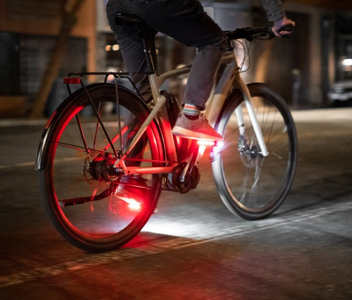 Cyclist riding bike at night with red and white light on pedals