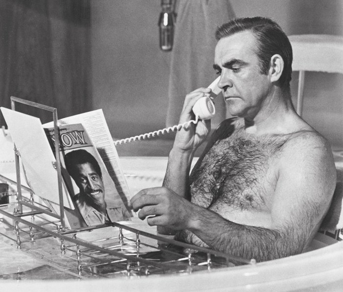 Actor Sean Connery reads and talks on telephone while in bathtub