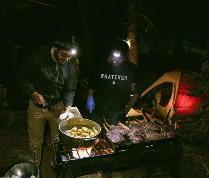 Two men cooking potatoes and steaks with headlamps on in campsite