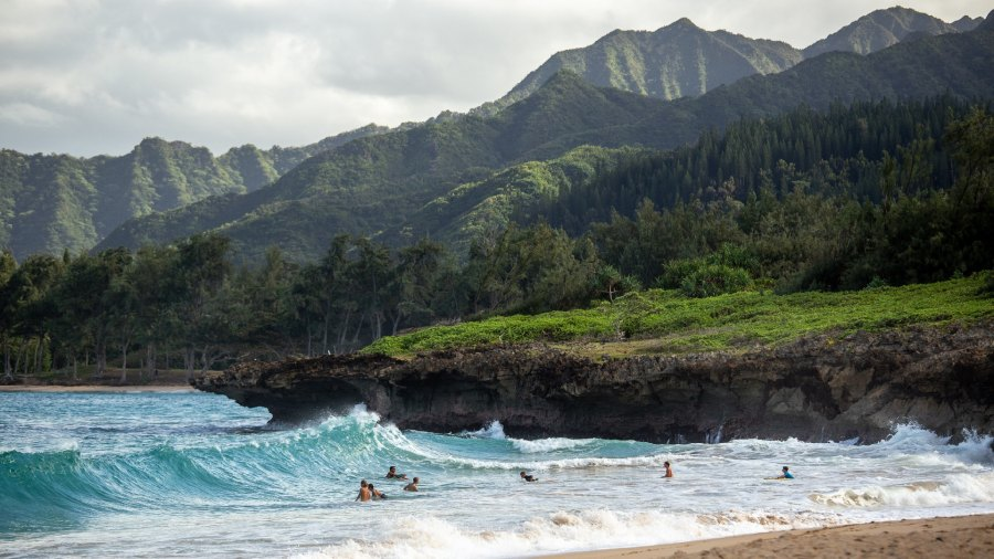 People swimming and surfing in water with Hawaii's volcanic terrain in background