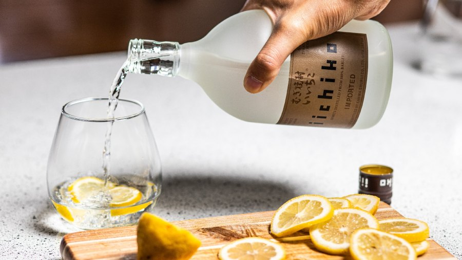 Man pouring bottle of clear spirit into glass next to cutting board of lemon slices