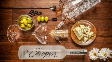 Dirty martini ingredients: bottle of vodka, glass, olives, and blue cheese on table