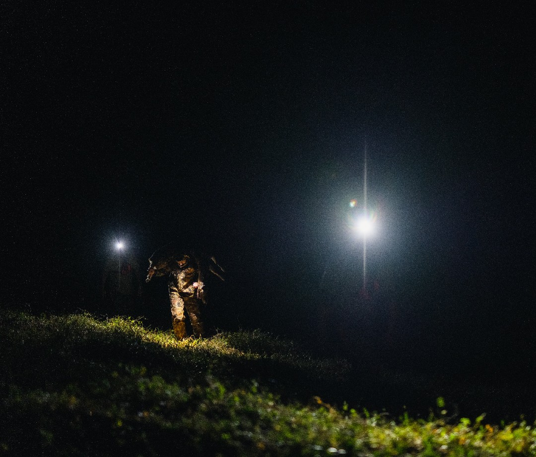 Working in the field at nighttime with bright spotlights