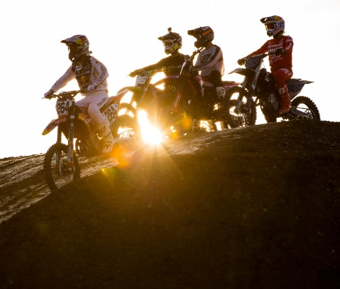 Motocross riders with sun behind them