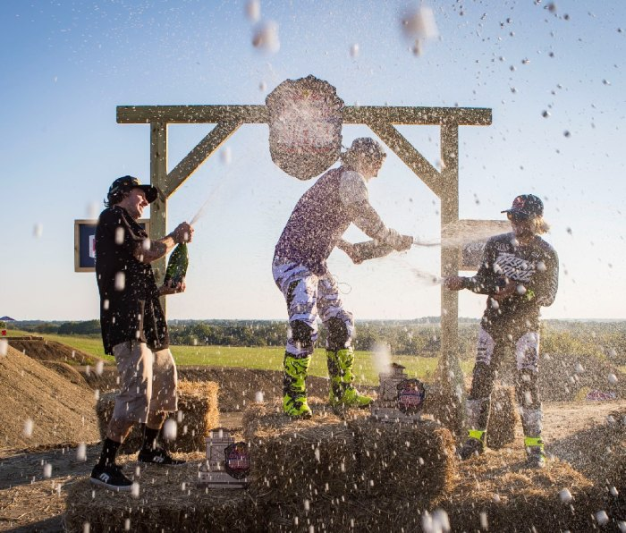 Motocross racers spraying Champagne on each other on podium