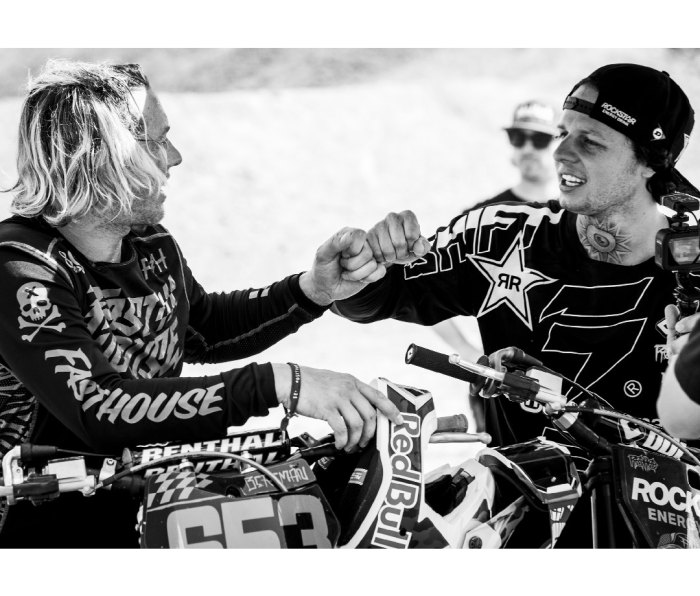 Two male motocross racers fist bump