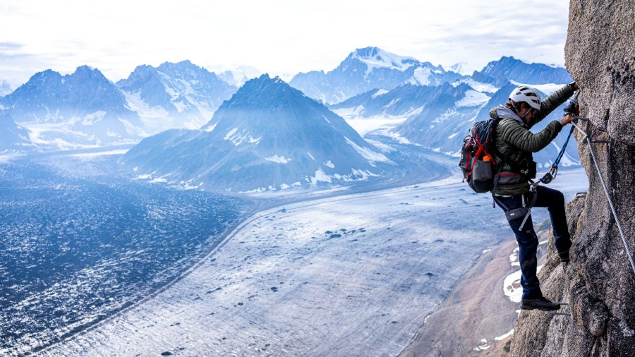 Man rock climbing with mountains in background