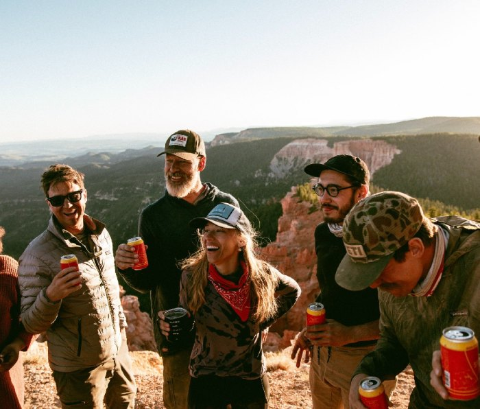 Group of men and women standing at top of ledge drinking beers