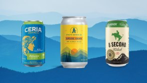 Three beer cans against hazy mountain ranges