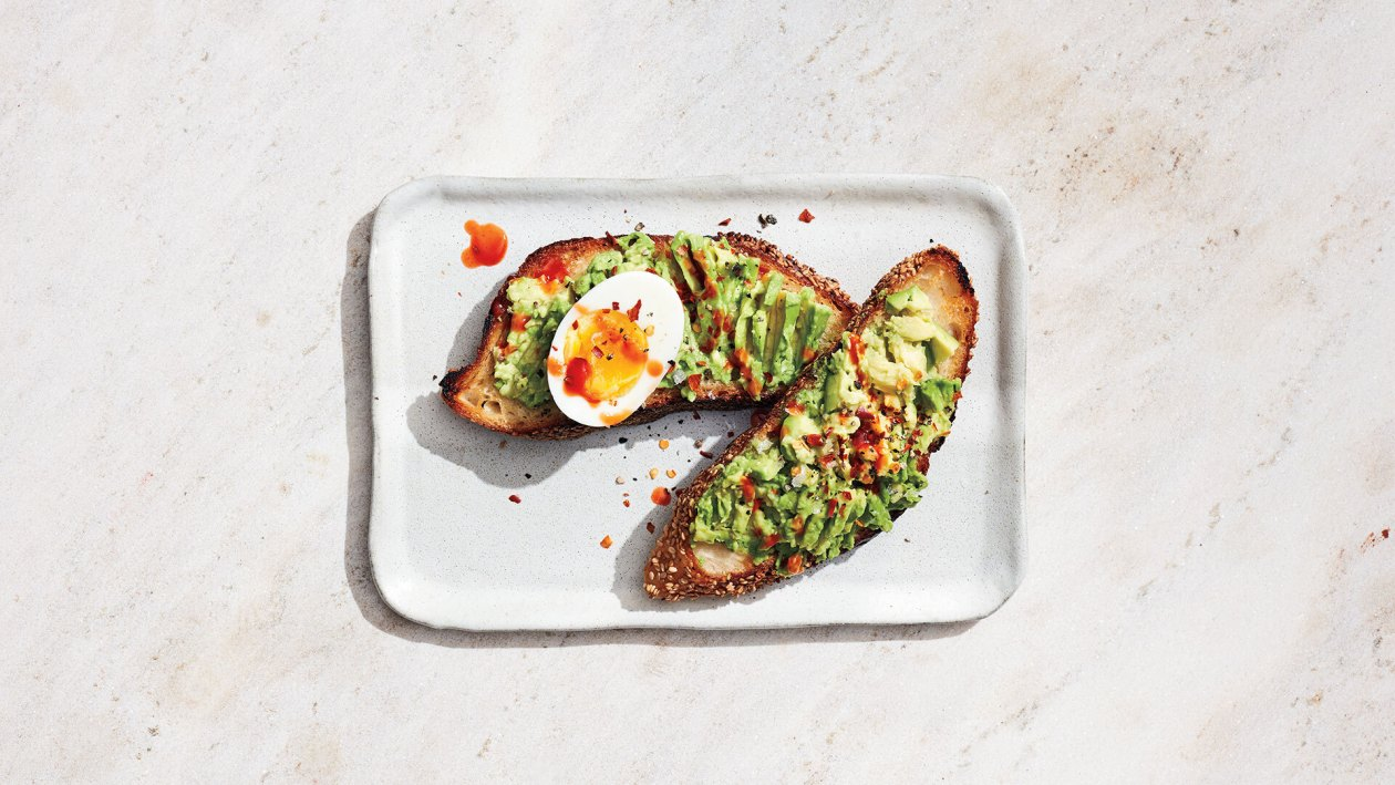 Rectangular plate with avocado toast and a hard boiled egg with hot sauce