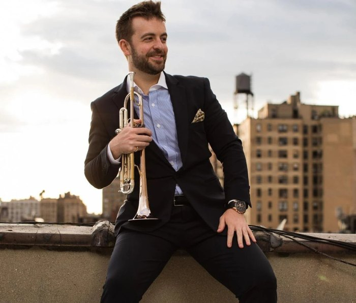 Man wearing suit sitting on rooftop with trumpet