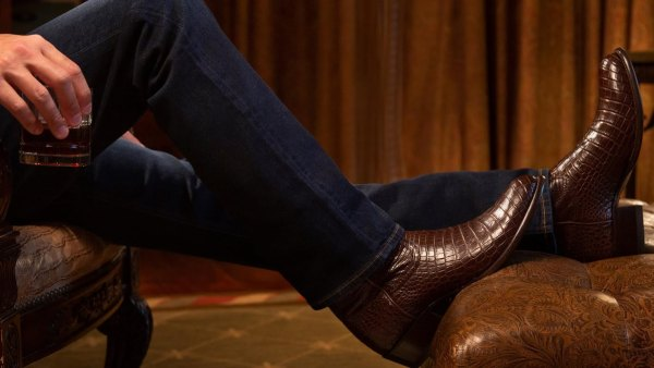 man wearing cowboy boots puts his feet up on a leather ottoman while holding a glass of whiskey