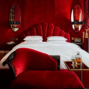 Design Hotels a red hotel room with a bed and a whiskey bottle on a table