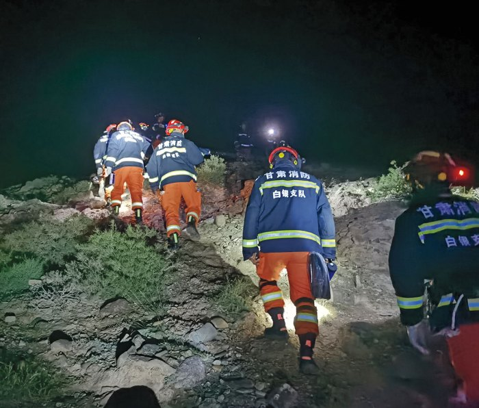 Rescue workers climbing hill in dark