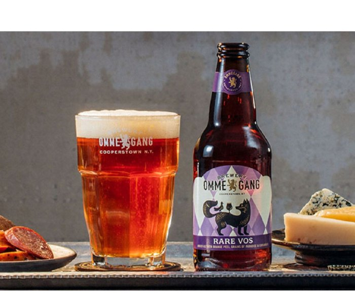 Filled glass and bottle of Ommegang Rare Vos beer on a table