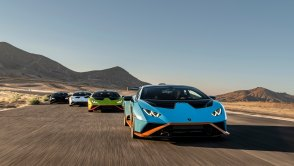 Blue 2021 Lamborghini Huracán STO leading a staggered row of cars on a race track