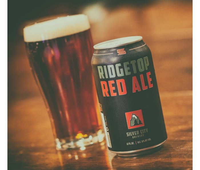 Filled pint glass and can of Silver City Ridgetop Red beer on a wooden table