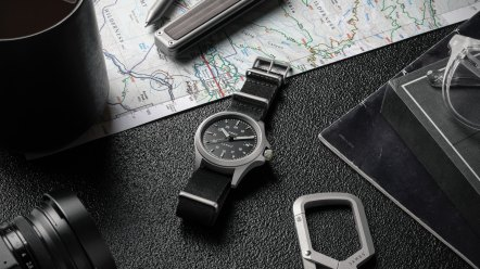 Timex x The James Brand Expedition North Titanium Watch on a black table surrounded by a map and a camera