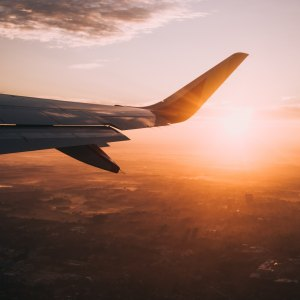 Travel tips for covid: window seat view of a plane taking off at sunrise