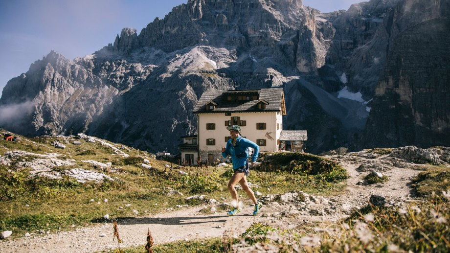 Trail runner with Dolomites mountains in background