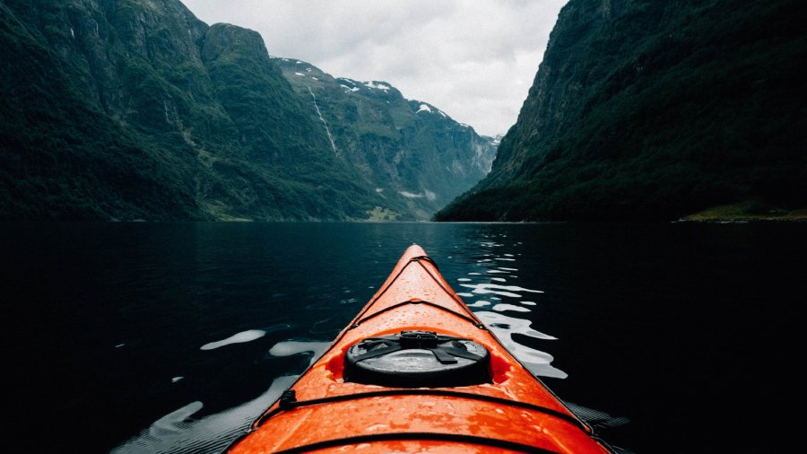 Orange kayak in water with steep valley sides and moody clouds