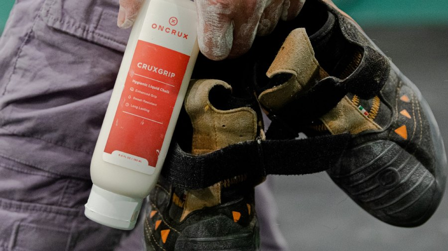 Closeup of hand holding a bottle of OnCrux Cruxgrip Liquid chalk and a pair of climbing shoes