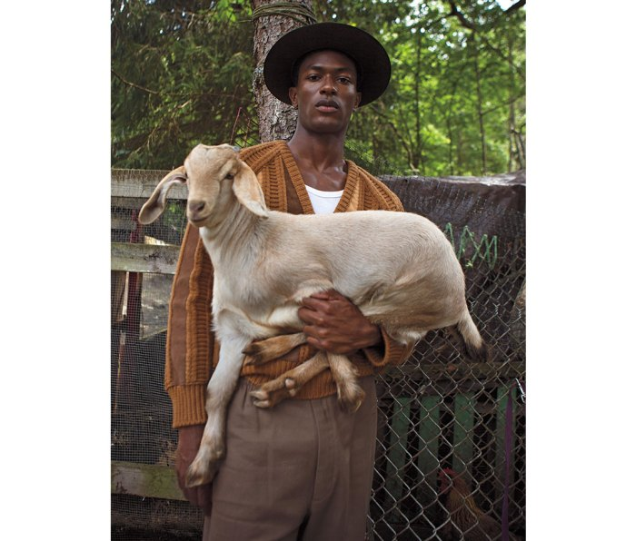 Black man in hat and auburn sweater holding a goat
