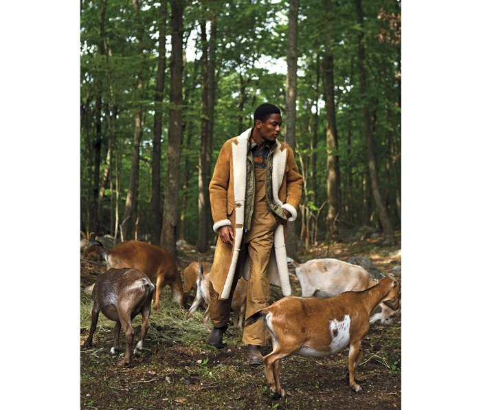 Black man wearing shearling coat in forest with goats