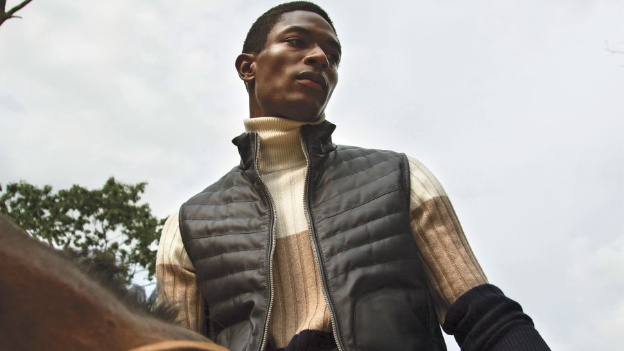 Black man riding horse wearing striped color-blocked turtle neck and black vest