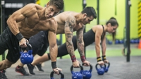 Men doing renegade rows with kettlebells