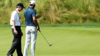 Dustin Johnson consults with a rules official on the fifth green after his ball moved during the final round of the U.S. Open at Oakmont Country Club.