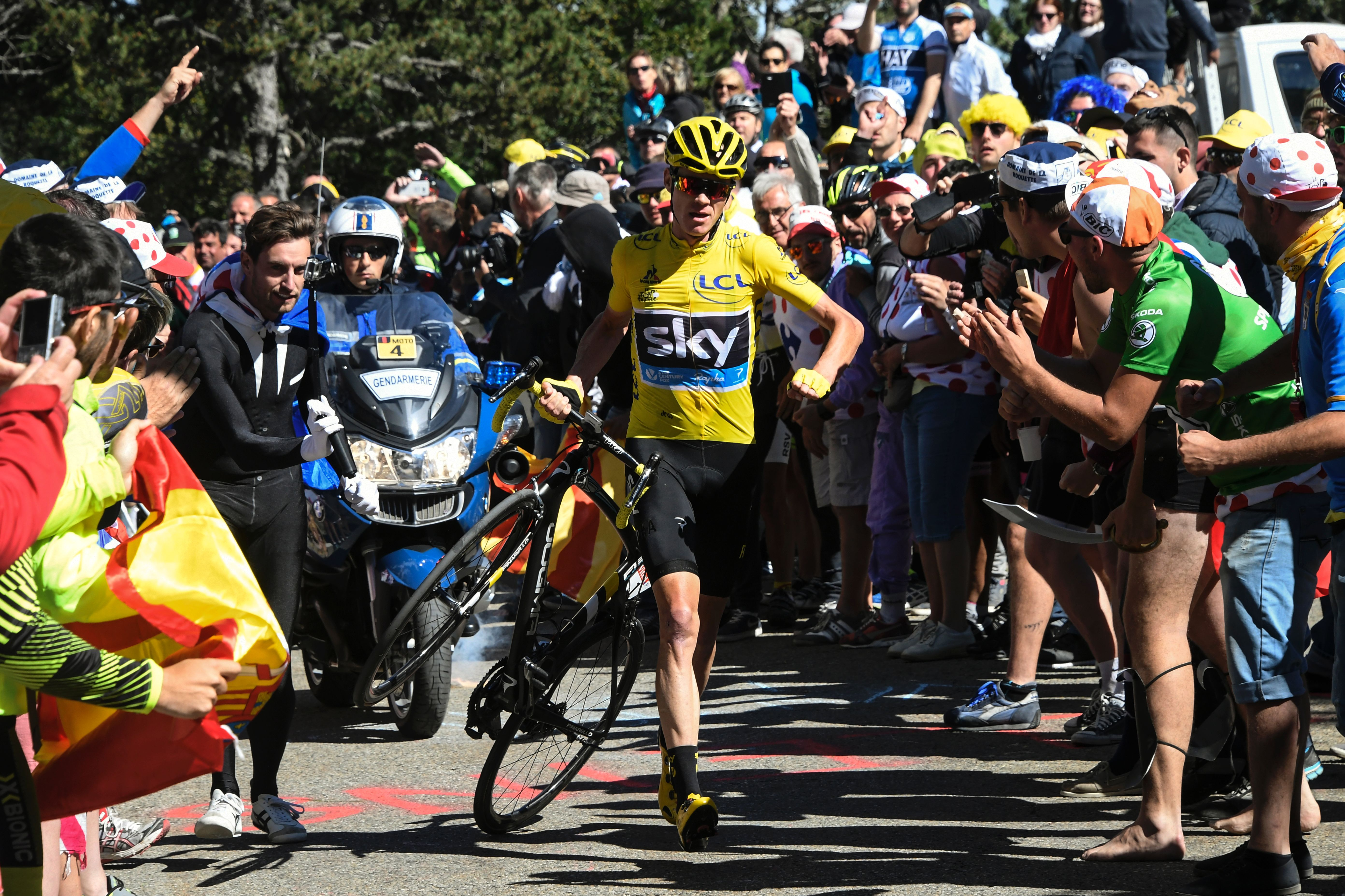 Froome carries his bike up Mont Ventoux after crashing.
