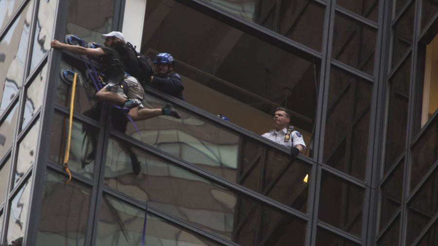 A climber is pulled into the building by police as he attempts an ascent of Trump Tower in New York, U.S., Wednesday, Aug. 10, 2016.