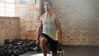 Man Doing Lunges With Kettle Bells