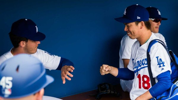 Kenta Maeda #18 of the Los Angeles Dodgers greets his teammates before a spring training game against the Colorado Rockies at Camelback Ranch on February 27, 2017 in Glendale, Arizona.