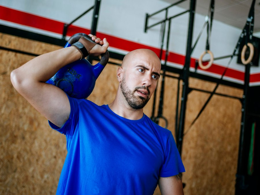 Man holding kettlebell in CrossFit-style gym.