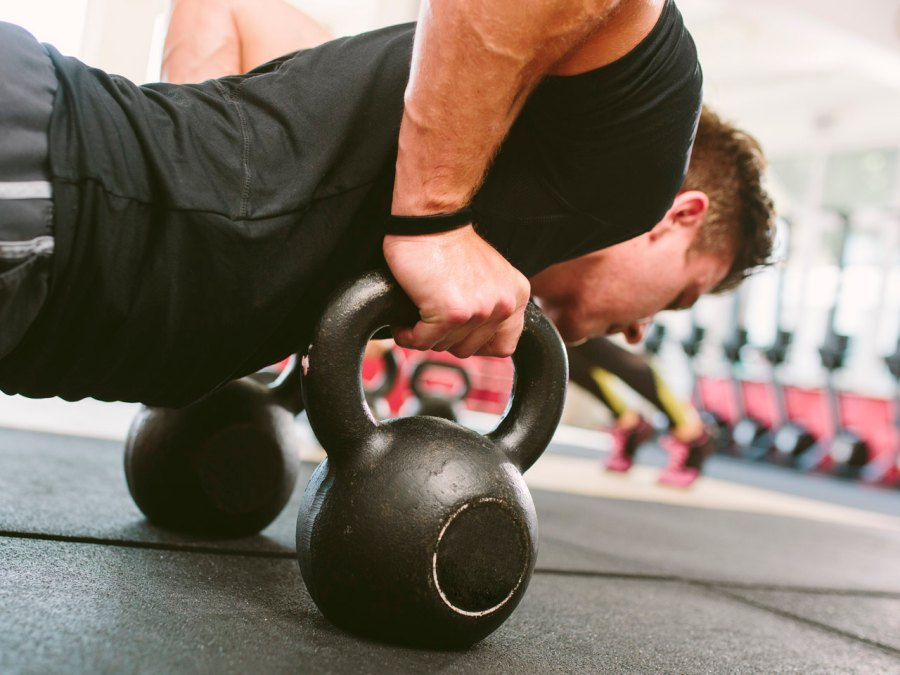 Man doing pushups with hands on kettlebells