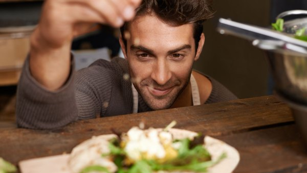 Man Sprinkling Onto Plate Of Food
