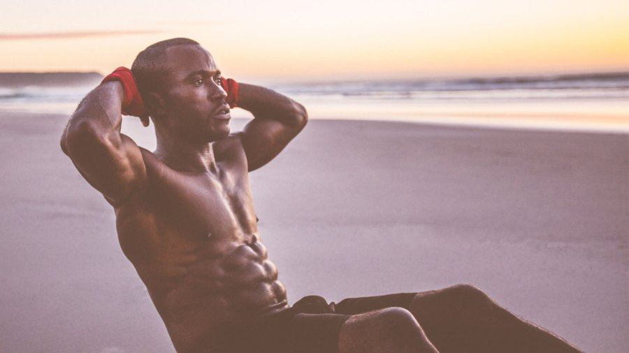 Man Doing Situps On The Beach