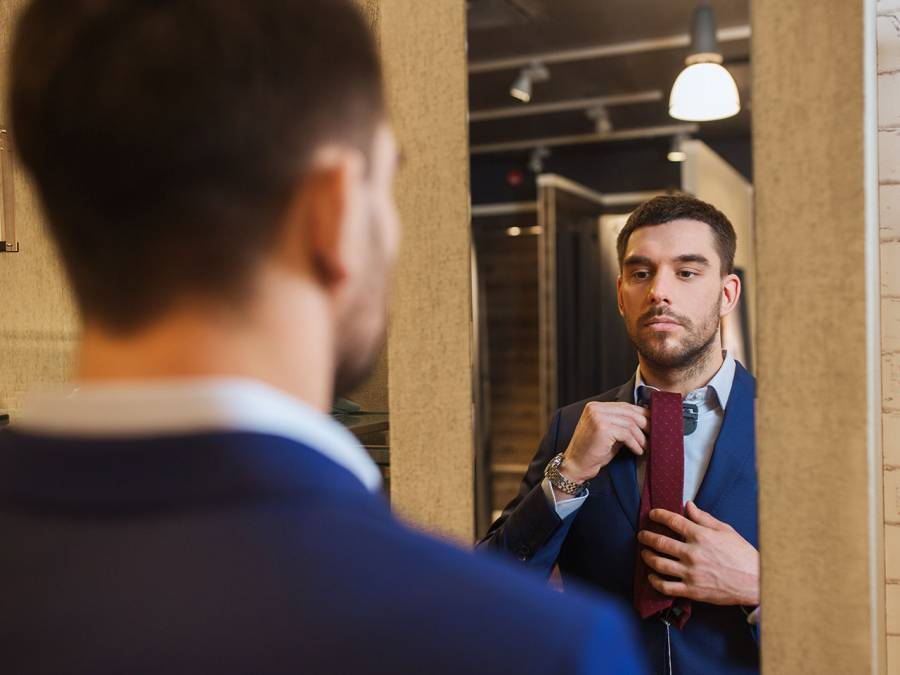 Man Tying Tie In Mirror