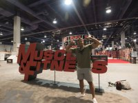 Man photographed besides Muscle & Fitness logo