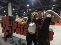 Man and woman photographed besides Muscle & Fitness logo